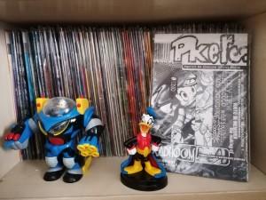 Le prime serie di Pk, Pk2 e Frittole, con un paio di action figure a caso e i numeri della fanzine Pkers
